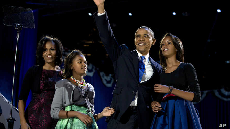 FILE - President Barack Obama waves as he walks on stage with first lady Michelle Obama and daughters Malia and Sasha at his election night party in Chicago, Nov. 7, 2012.