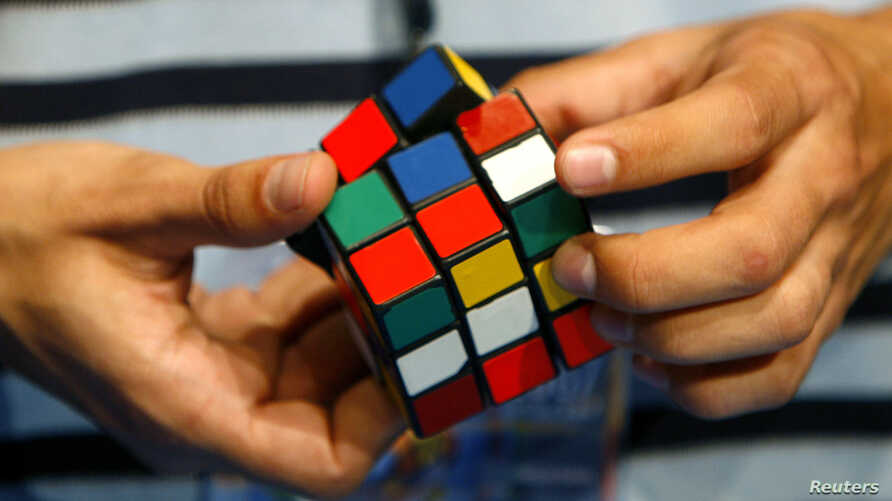 FILE - A competitor attends the World Rubik's Cube Championship in Budapest.