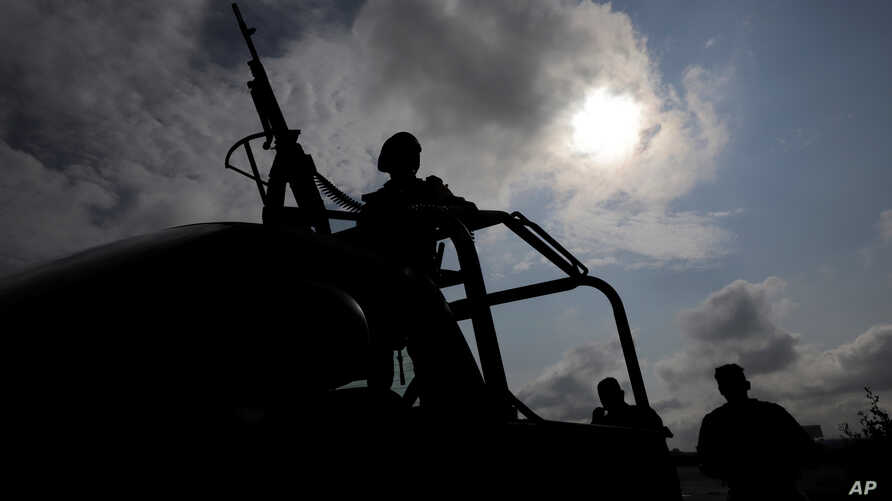 Military personnel are silhouetted while keeping watch at the perimeter of an area evacuated because of a gas leak caused by a pipeline theft in Puebla, Mexico, Sept. 12, 2018. A similar presumed fuel theft in 2017 left 10 dead and 13 detained with e