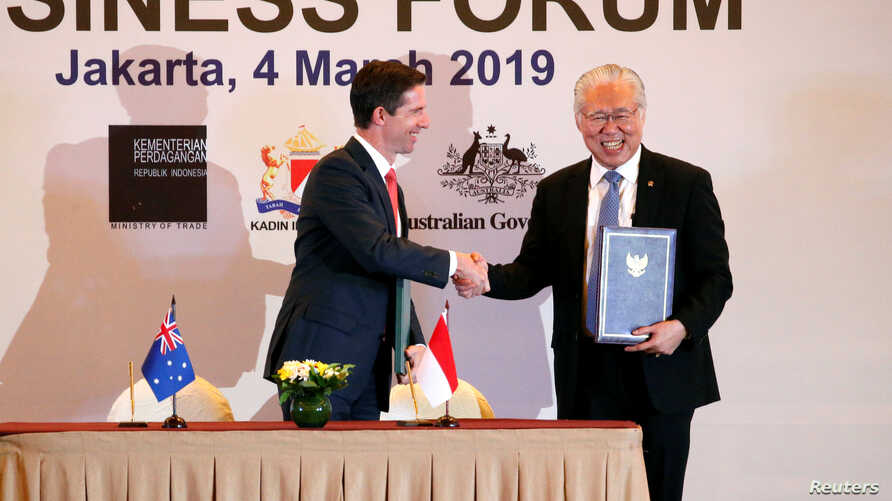 Indonesia's Trade Minister Enggartiasto Lukita and Australia's Minister of Trade, Tourism and Investment Simon Birmingham shake hands after signing an economic partnership agreement aimed at boosting trade and investment, March 4, 2019, in Jakarta.