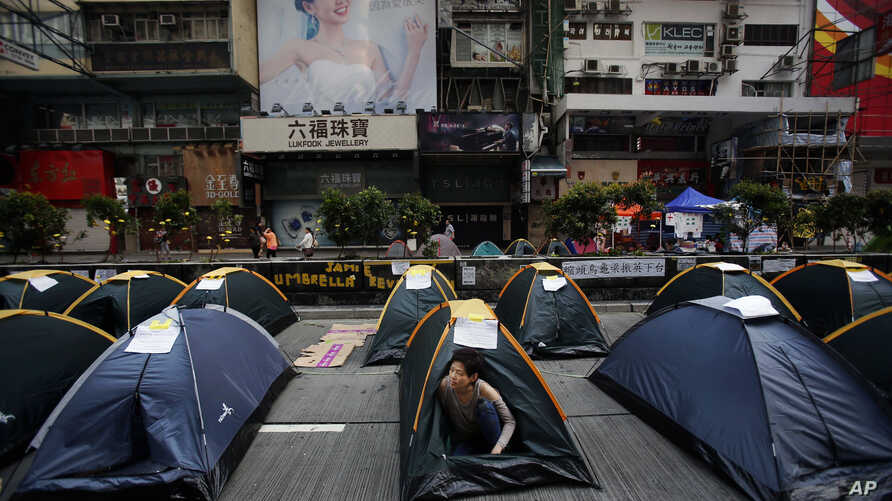 AP10ThingsToSee - A pro-democracy protester wakes from her tent in the occupied area by them at the Mong Kok district of Hong Kong, Thursday, Oct. 16, 2014. Police briefly scuffled with protesters camped out in Hong Kong's streets early Thursday, but