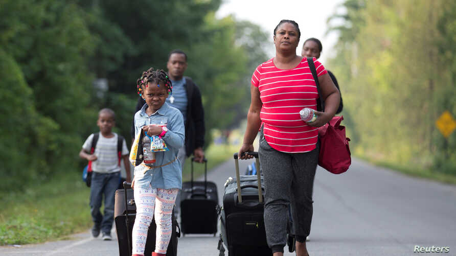 A family that stated they are from Haiti walk to the US-Canada border to cross into Canada from Champlain, New York, U.S. August 11, 2017. REUTERS/Christinne Muschi - RTS1BEGH