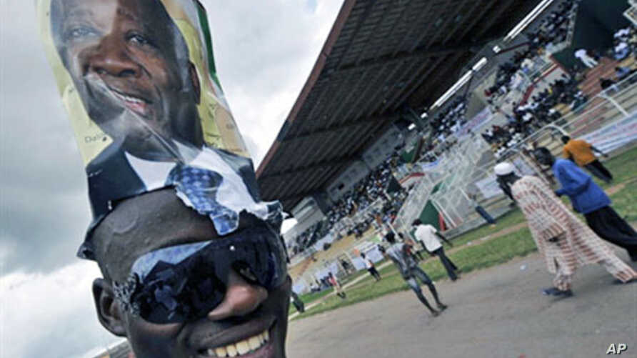 A supporter wears a poster on his head of Ivory Coast Laurent Gbagbo during a rally at a stadium in Bouake ahead of the 31 Oct 2010 elections (File)