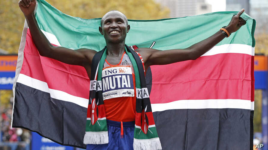 Geoffrey Mutai of Kenya holds the Kenyan flag after winning the men's division of the New York City Marathon, Nov. 3, 2013.