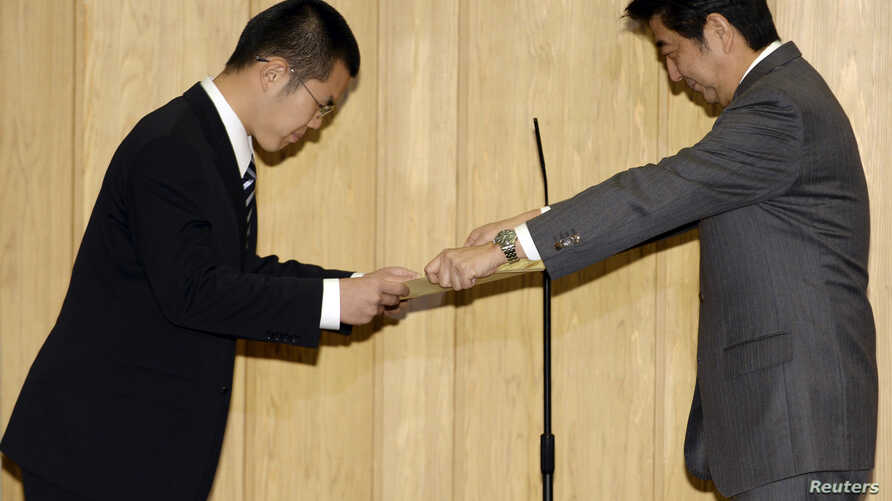 Shanghai-born Yan Jun, receives a certificate of appreciation from Japan's Prime Minister Shinzo Abe for saving a nine-year-old boy from a typhoon-swollen river in Osaka on Sept. 16.