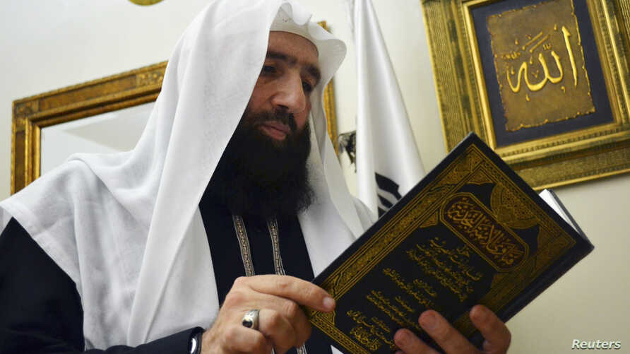 Islamist preacher Omar Bakri takes a look at a religious book during an interview with Reuters at his home in Tripoli, northern Lebanon, May 24, 2013.