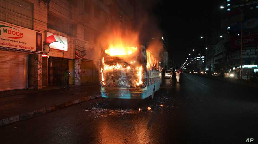 A bus stands in flames after it was set afire by opposition supporters trying to defy a ban on protests, in Dhaka, Bangladesh, Friday, Oct. 25, 2013.