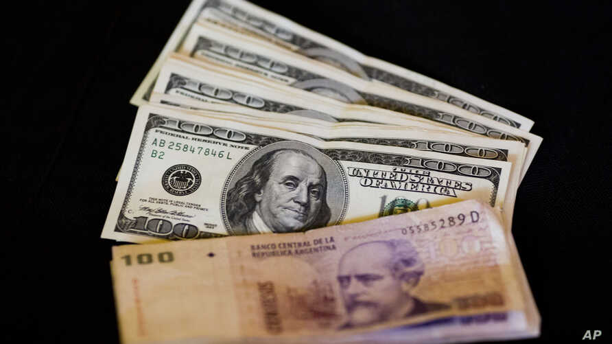FILE - U.S. dollar bills and Argentine pesos are displayed for the photographer on a table at a currency exchange business in Buenos Aires, Argentina, Jan. 23, 2014.