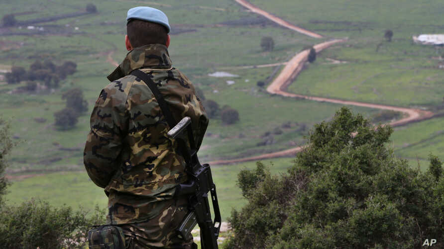 "FILE - A Spanish U.N. peacekeeper looks to the U.N-demarcated ""Blue Line"" border between Lebanon and Israel, Feb. 24, 2015."