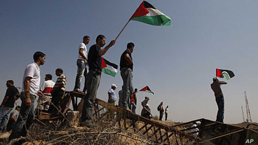 Palestinians hold Palestinian flags during a demonstration near the border between Gaza and Israel (file photo)