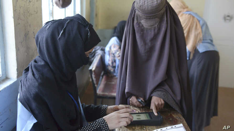 A woman voter, right, has her finger scanned before casting her vote during parliamentary elections in Kandahar, south of Afghanistan, Oct. 27, 2018.