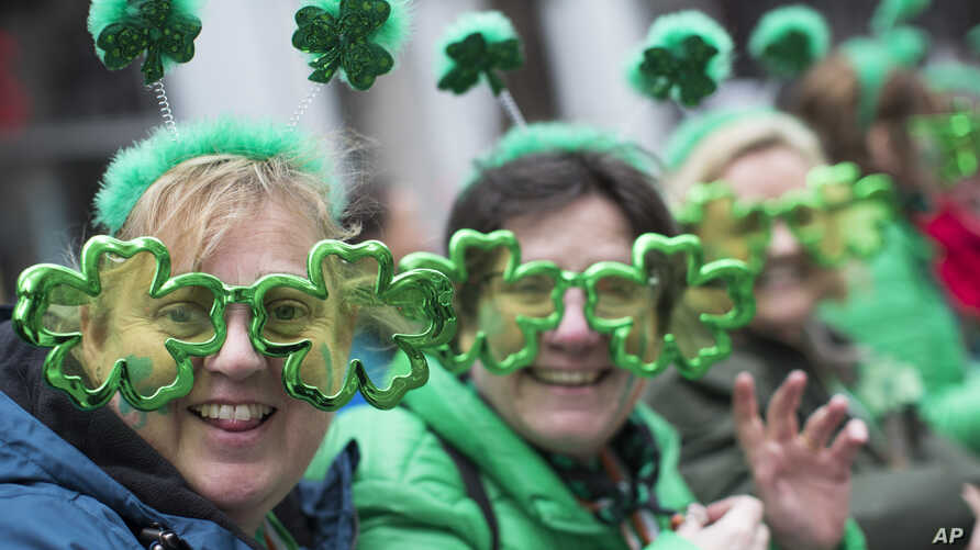 Sharon Keely, left, of Dublin, watches as participants march up Fifth Avenue during the St. Patrick's Day Parade, March 16, 2019, in New York.