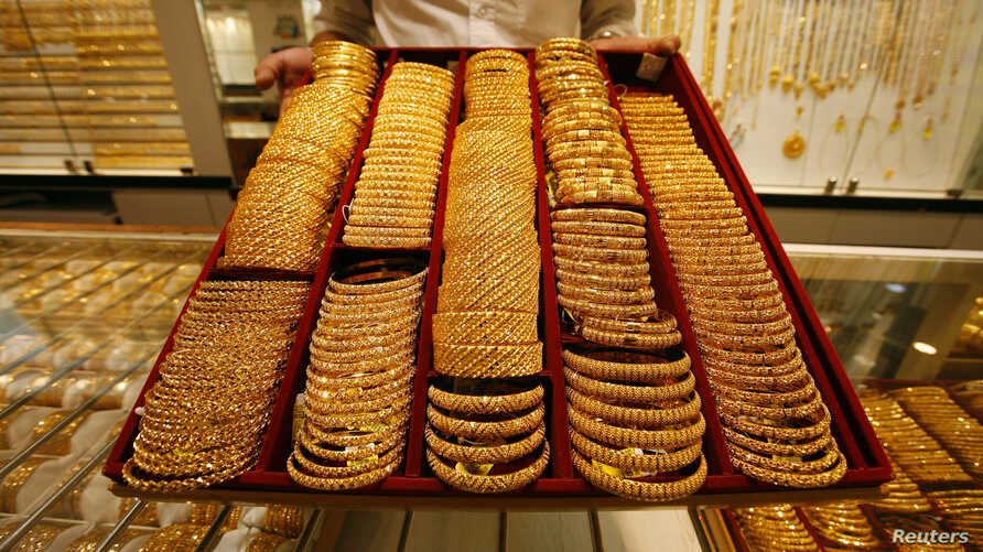 FILE - A salesman displays a tray of gold bangles at a jewelery shop in Singapore, Oct. 7, 2009.