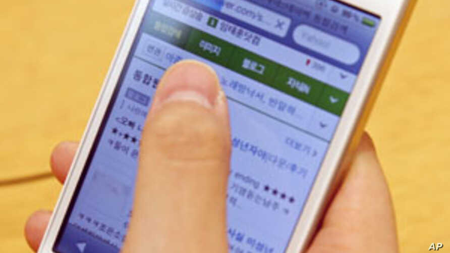 A woman uses an Apple iPhone 4 smartphone for Web surfing during a photo opportunity at an Apple store in Seoul, May 24, 2011