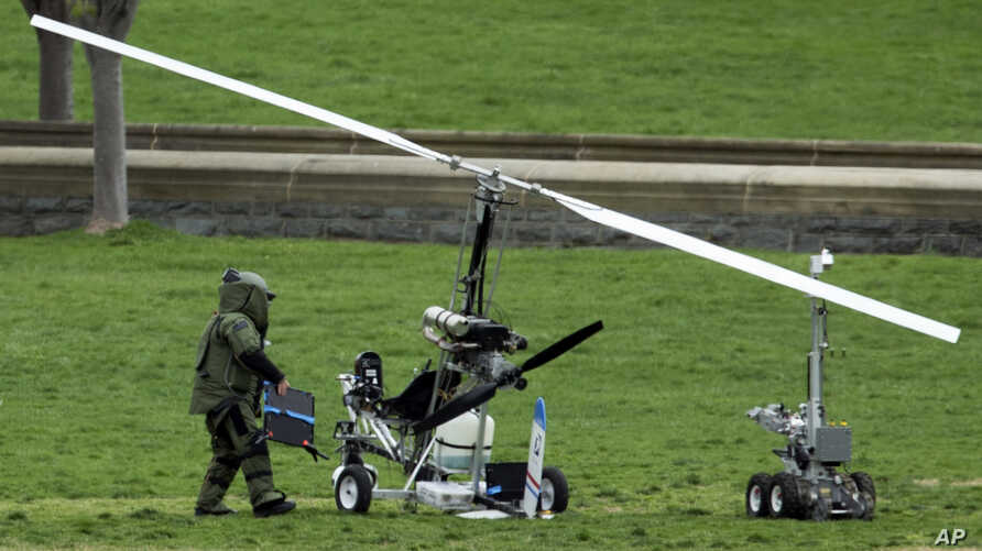 A member of a bomb squad checks a small helicopter after a man landed on the West Lawn of the Capitol in Washington, April 15, 2015.