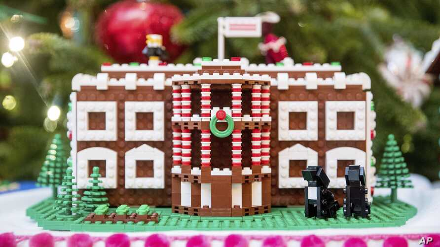 FILE -  In this Tuesday, Nov. 29, 2016 file photo a LEGO model of the White House, one of fifty-six LEGO gingerbread houses, one for each state and territory, is displayed in the trees in the State Dinning Room at the White House during a preview of