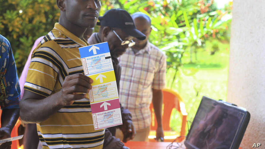 In this photo taken Oct 16, 2018, a man demonstrates using an electronic voting machine that will be used later in the year for the next election in Beni, Eastern Congo.