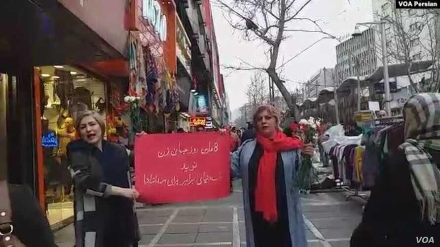 Two unveiled Iranian women mark International Women's Day on Tehran's Valiasr Street, March 8, 2019, holding a red sign that says the occasion brings hope for a just world for all humanity.