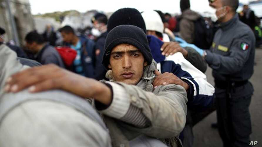 A man fleeing the unrest in Tunisia looks on as he and others arrive at the southern Italian island of Lampedusa (file photo)