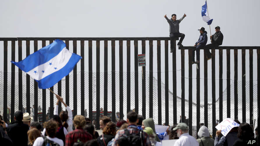Migrant CaravanCentral American migrants sit on top of the border wall on the beach in San Diego during a gathering of migrants living on both sides of the border, April 29, 2018.