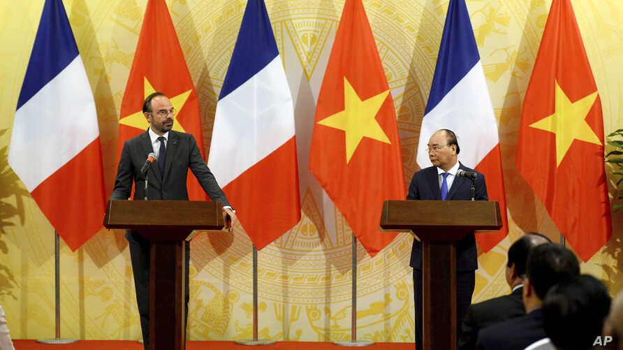 French Primer Minister Edouard Philippe (L) looks on as Vietnam's Prime Minister Nguyen Xuan Phuc speaks during their joint press conference at International Convention Center in Hanoi, Nov. 2, 2018.