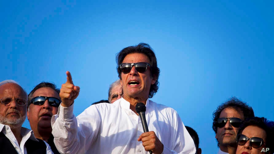 Pakistan's cricketer-turned-politician Imran Khan, center, is surrounded by aides as he addresses to his supporters near the parliament building in Islamabad, Pakistan, Aug. 27, 2014.