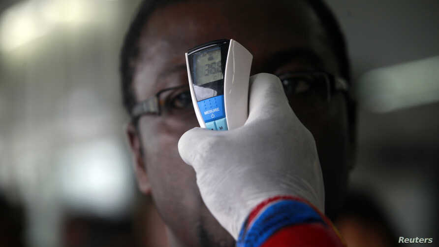 A health worker takes a passenger's temperature with an infrared digital laser thermometer at the Felix Houphouet Boigny international airport in Abidjan, Ivory Coast, Aug. 13, 2014.