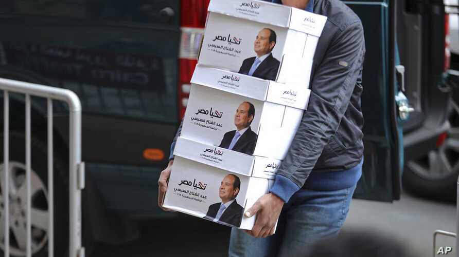 """This undated image released Jan. 24, 2018 on the official Facebook account of Egyptian President Abdel-Fattah el-Sissi, shows workers carrying boxes  that bear the president's image and the phrase """"long live Egypt!"""" in Cairo Egypt. The boxes co..."""