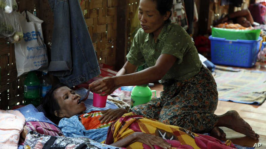 A family member takes care of a HIV patient at HIV/AIDS care center founded by Phyu Phyu Thin, a parliament member of Burma's Opposition Leader Aung San Suu Kyi's National League for Democracy Party, in outskirts of Rangoon, Mar. 1, 2014.