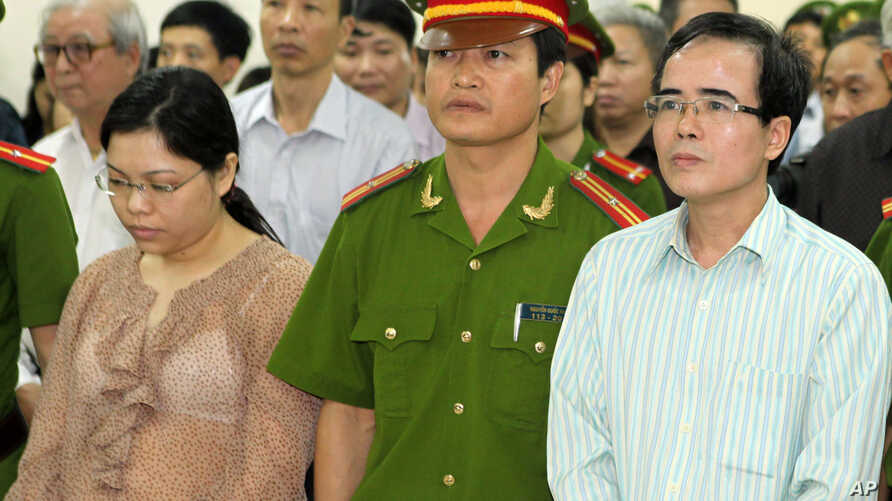 FILE - A U.S-trained lawyer and well-known dissident Le Quoc Quan, right, listens to the judge during his trial in Hanoi, Vietnam.