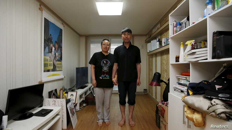 Kim Young-lae, right, and Kim Sung-sil, parents of Kim Dong-hyuk, a high school student who died in the Sewol ferry disaster, pose for a photograph in their son's room, Ansan, South Korea, April 8, 2015.