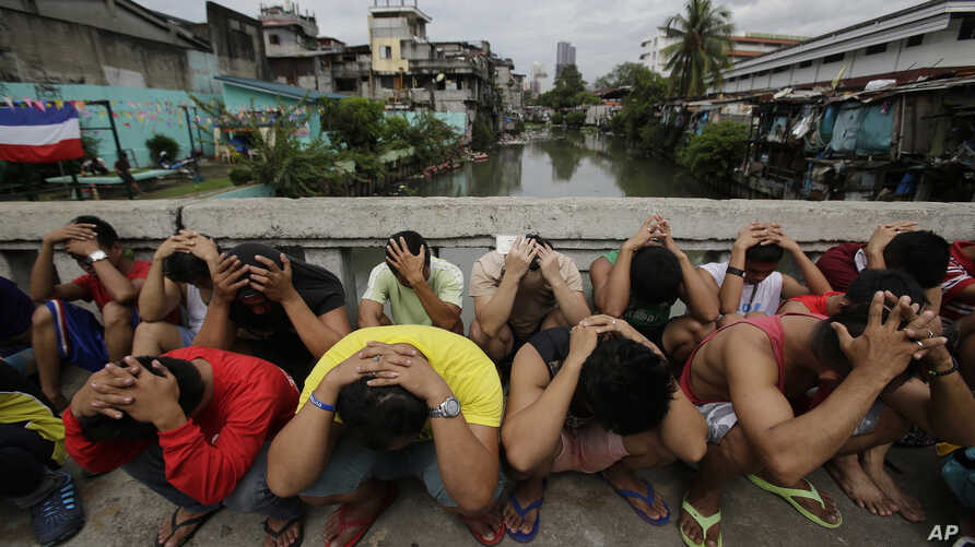 """FILE - Filipino men place their hands over their heads as they are rounded up during a police operation as part of the continuing """"War on Drugs"""" campaign of Philippine President Rodrigo Duterte in Manila, Philippines, Oct. 7, 2016."""