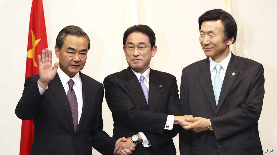 Japanese Foreign Minister Fumio Kishida, center, Chinese Foreign Minister Wang Yi, left, and South Korean Foreign Minister Yun Byung-se, right, pose for photographers prior to the official banquet of the trilateral foreign ministers meeting in Tokyo,