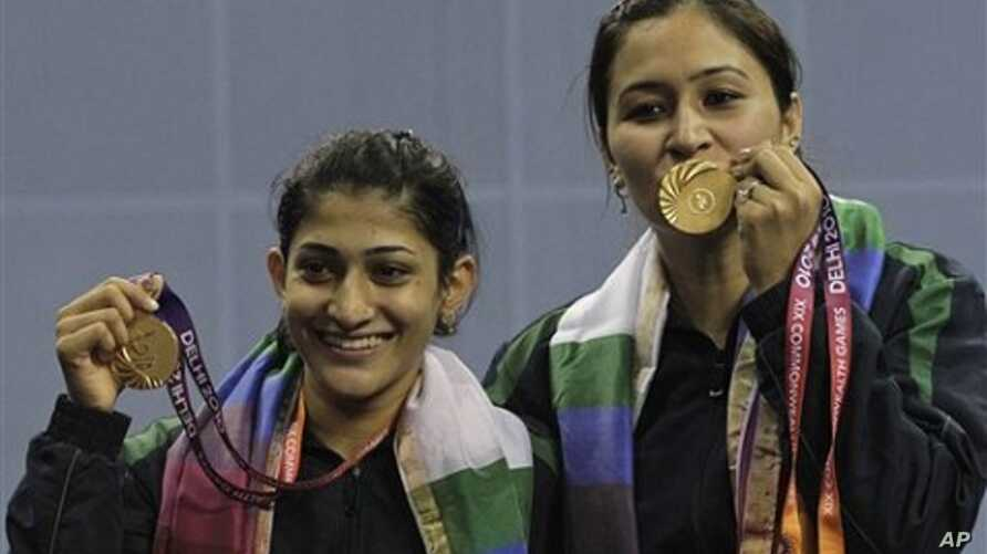 India's Jwala Gutta, right, and Ashwini Ponnappa Machimanda show the gold medals they won in the women's badminton doubles event during the Commonwealth Games at Siri Fort Sports Complex in New Delhi, India, 14Oct.  2010.