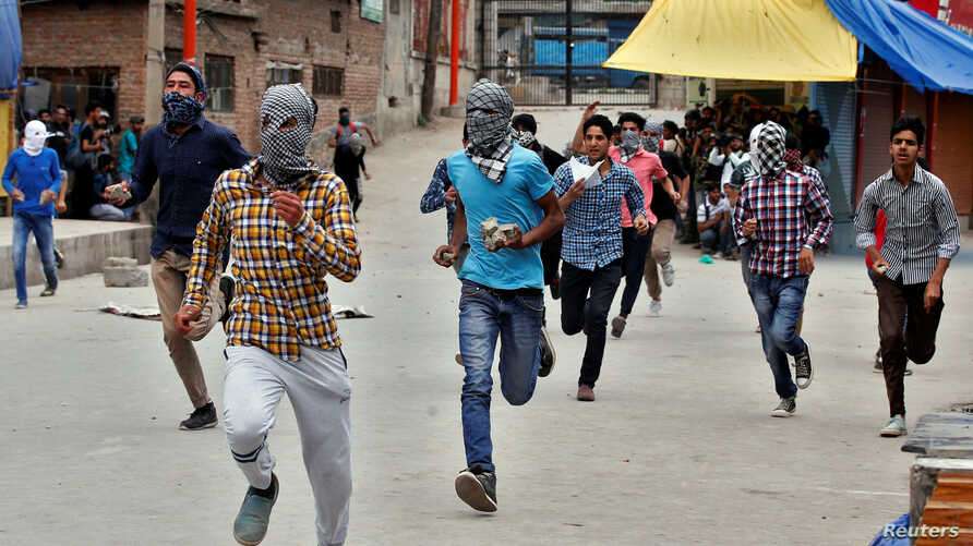 Protesters run as they prepare to hurl stones toward the Indian police during a protest after Friday prayers, in Srinagar, May 26, 2017.