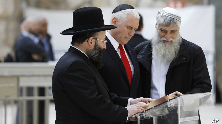 U.S. Vice President Mike Pence, center, looks at a book together with Western Wall Heritage Foundation Director General Mordechai Elias, right, and Rabbi of the Western Wall Shmuel Rabinovitch during a visit to the Western Wall, Judaism's holiest pra