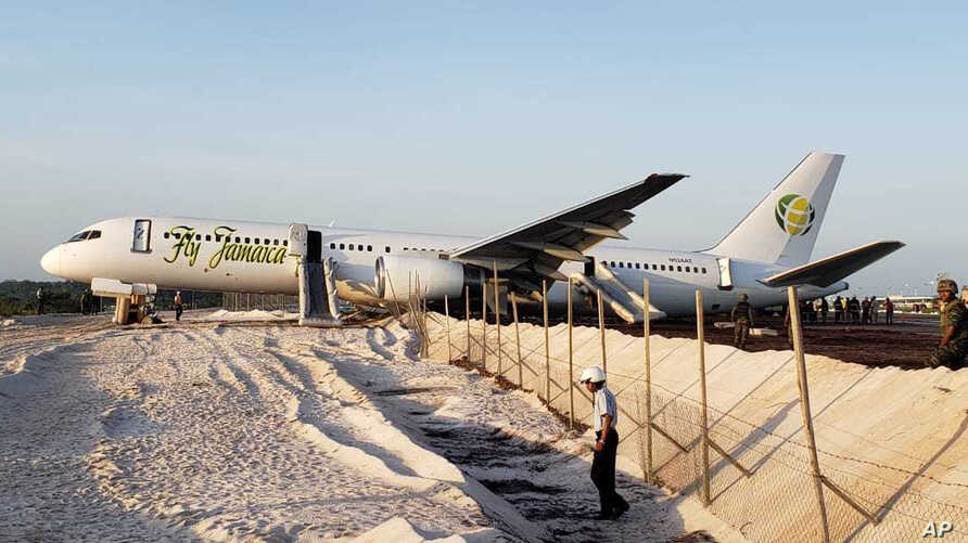A Fly Jamaica Boeing 757-200 aircraft, which overshot the runway, sits at the northeastern takeoff end of the runway at the Cheddi Jagan International Airport, in Georgetown, Guyana, Nov. 9, 2018.