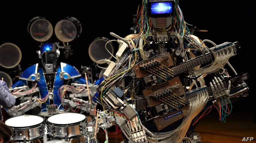 """Robot guitarist """"Mach"""" and robot drummer """"Ashura"""" (L), members of a robot rock band """"Z-Machines"""", perform music during the two day art and technology event """"Maker Faire Tokyo"""" at the National Museum of Emerging Science and Innovation in Tokyo on Nove"""