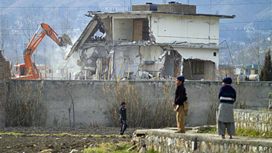 A police commando stands guard as authorities use heavy machinery to demolish Osama bin Laden's compound in Abbottabad, Pakistan, February 26, 2012.