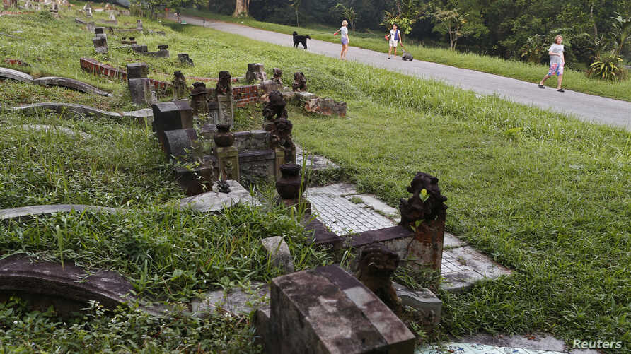 FILE - Residents in the nearby vicinity take their morning walks with their dogs at Bukit Brown cemetery in Singapore, Nov. 27, 2012.
