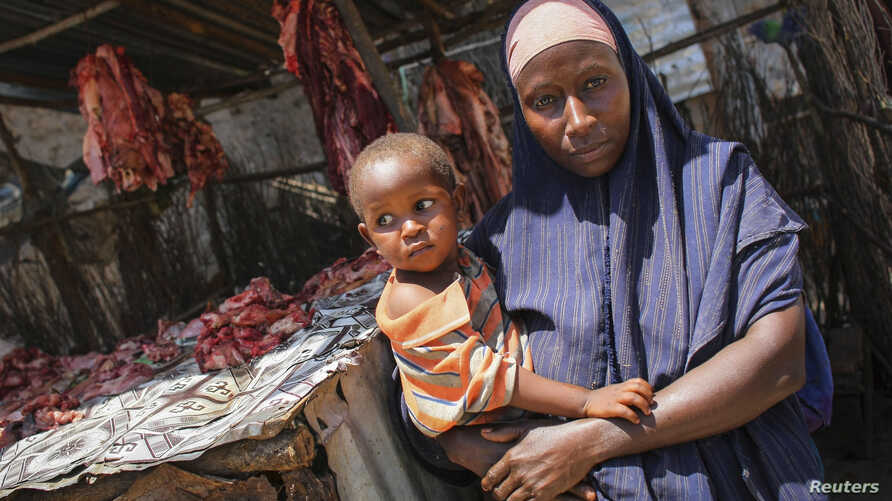 A Somali woman selling meat from a kiosk holds her child in a market area in the centre of the southern port city of Kismayo, south of Mogadishu, October 7, 2012