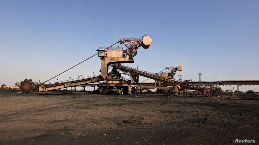 FILE - A universal machine stands in open ground near the conveyor belt at coal handling plant at the Pakistan Steel Mills on the outskirts of Karachi, Pakistan, February 8, 2016.