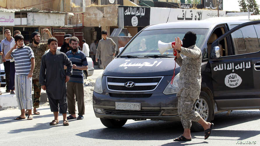 An Islamic State militant uses a loud-hailer to announce to residents of Tabqa city that Tabqa air base has fallen to Islamic State militants, in nearby Raqqa city August 24, 2014.