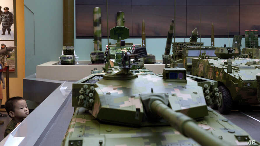 FILE - A child peers at a model tank during an exhibition to mark the 90th anniversary of the founding of the People's Liberation Army at the military museum in Beijing, China, Aug. 1, 2017.