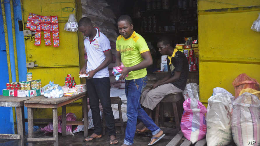 A man, center, walks out of a re-opened store after he shopped for daily goods near West Point slum in Monrovia, Liberia, Aug. 30, 2014.
