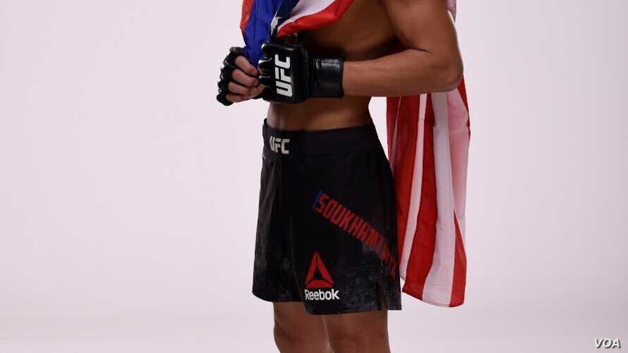 Andre Soukhamthath Lao American UFC Fighter Holding Lao and American Flag.