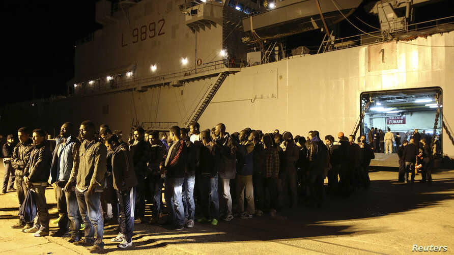 Migrants stand in line at the Sicilian harbour of Augusta, April 9, 2014.
