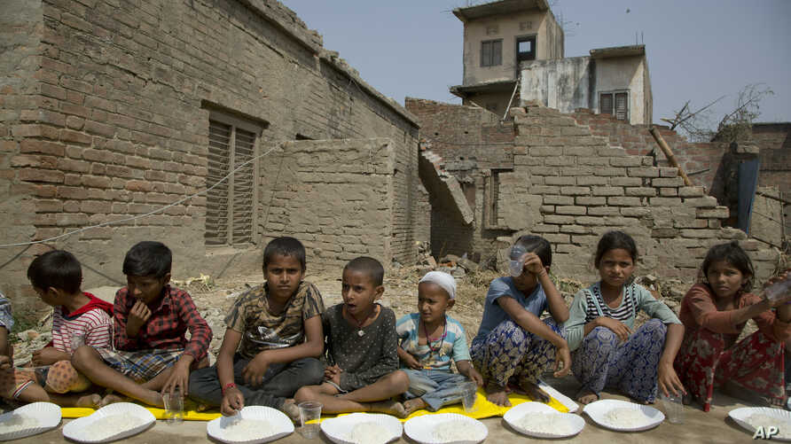 Nepalese children wait for the food to be distributed as they sit next to their houses damaged in a rainstorm in Bara district, 125 kilometers (75 miles) south of Kathmandu, Nepal, April 1, 2019.