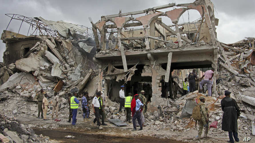 Somali security forces and others gather and search for bodies near destroyed buildings at the scene of Saturday's blast, in Mogadishu, Somalia, Oct. 15, 2017.
