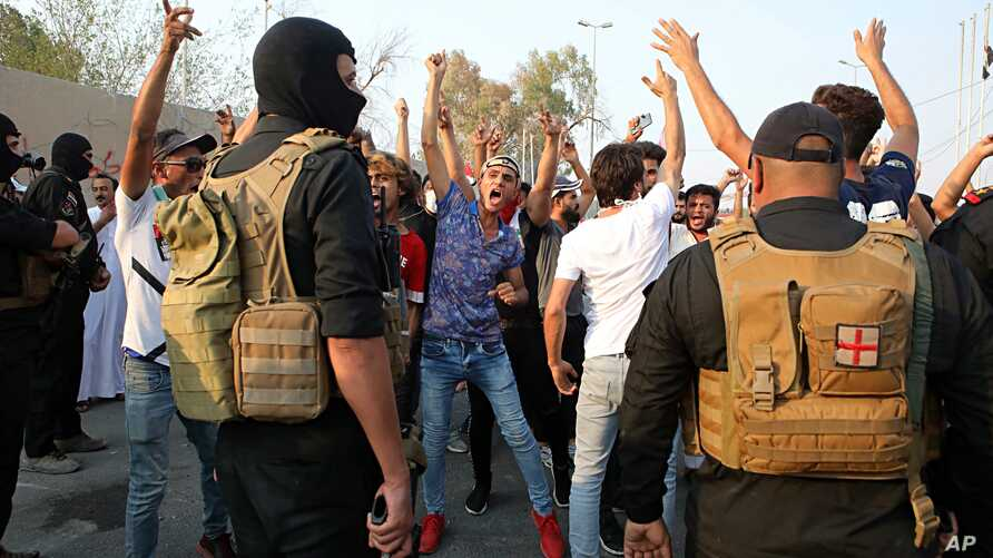 Protesters chant anti-government slogans while security forces prevent them from storming the governor's building during protests demanding better public services and jobs in Basra, 340 miles (550 km) southeast of Baghdad, Iraq, Sept. 5, 2018.